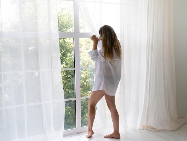 サイドビューの女性、窓の外を見て