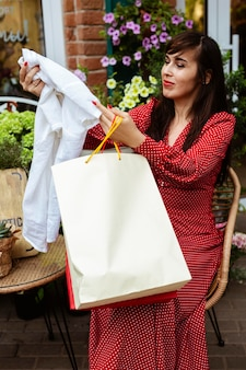 Vista laterale della donna che esamina i vestiti di acquisto di vendita