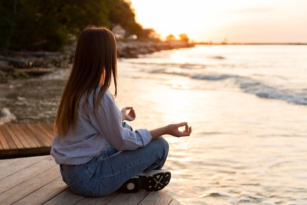 Side view woman looking at the sea at sunset with copy space