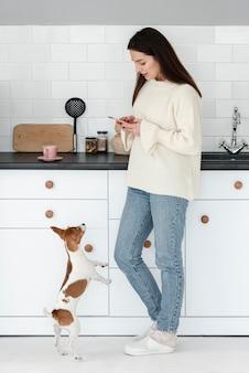 Vista laterale della donna che esamina smartphone con il cane