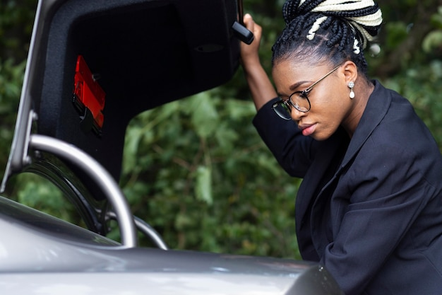 Side view of woman looking through the trunk of her car