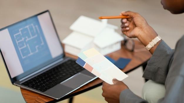 Vista laterale della donna che fa piani per ridipingere la casa con il laptop