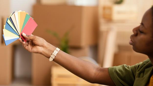 Vista laterale della donna che fa piani per ristrutturare casa utilizzando la tavolozza dei colori