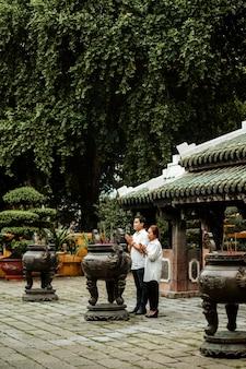Vista laterale della donna e dell'uomo che pregano al tempio con incenso che brucia