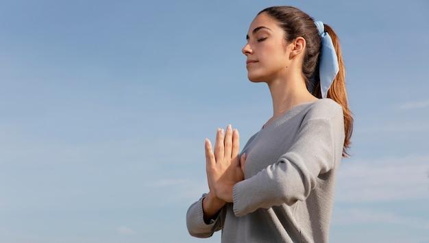 自然の中で瞑想する側面図の女性