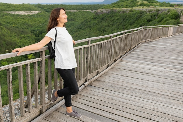 Side view of woman in nature posing on bridge