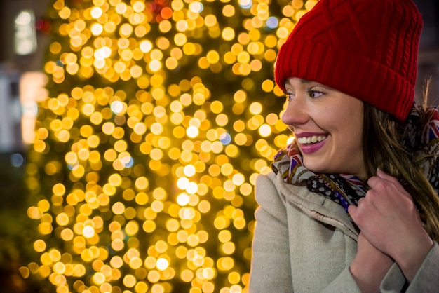 Вид сбоку женщина на праздничном рождественском рынке в ночное время счастливая женщина, глядя вверх с рождественский свет в ночное время