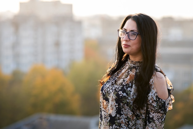 Side view of woman outdoors in glasses with copy space