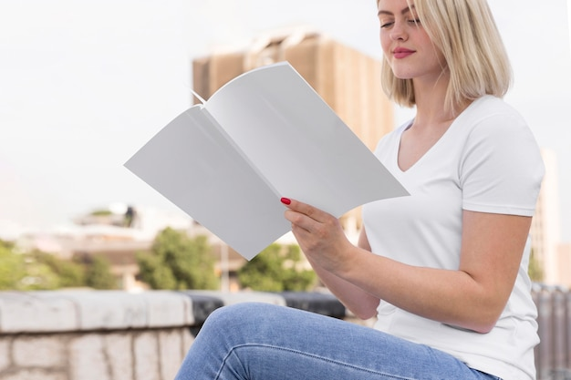 Side view of woman outdoors holding and reading book