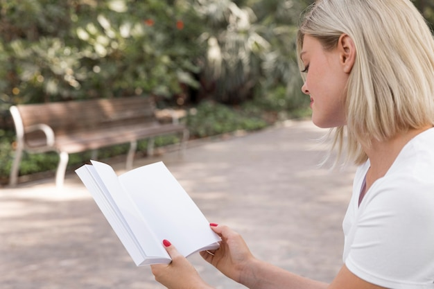 Side view of woman outdoors holding and reading a book