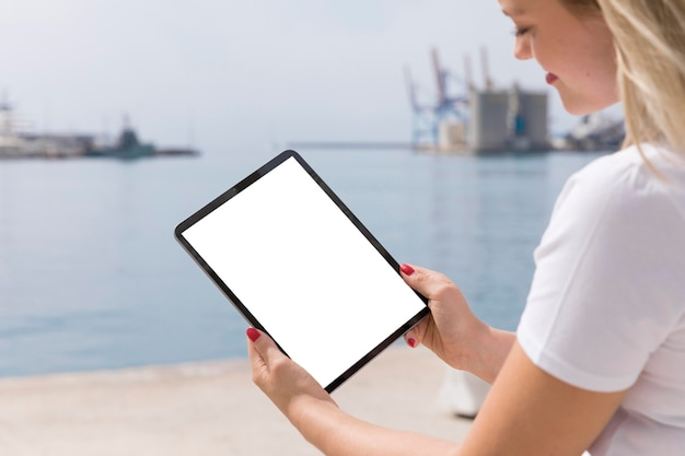 Side view of woman outdoors holding tablet