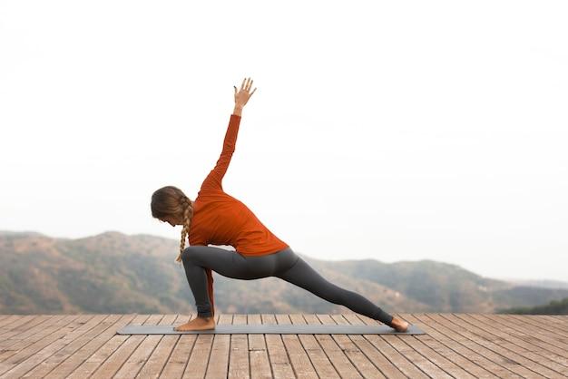 Vista laterale della donna all'aperto nella natura che fa yoga