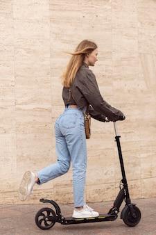 Vista laterale della donna all'aperto equitazione scooter elettrico