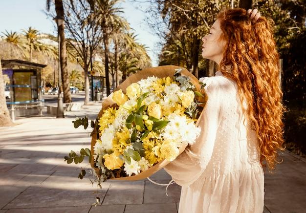 Vista laterale della donna all'aperto con bouquet di fiori primaverili