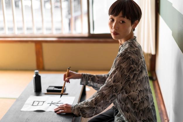 Вид сбоку женщина рисует буквы