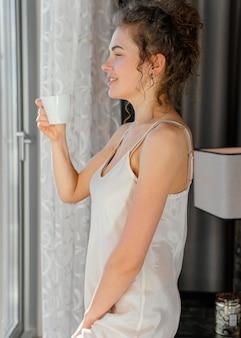 Donna di vista laterale in pijama che beve caffè
