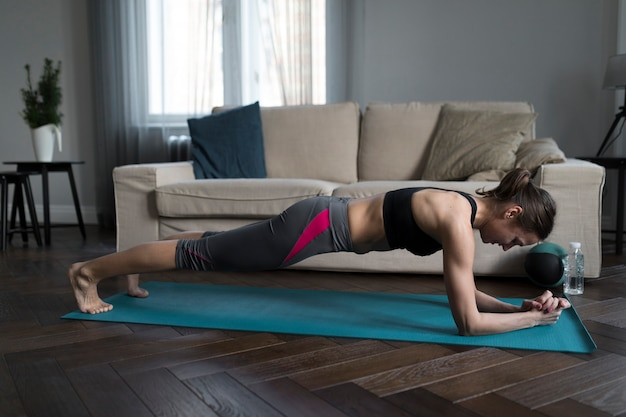 Side view of woman planking on yoga mat