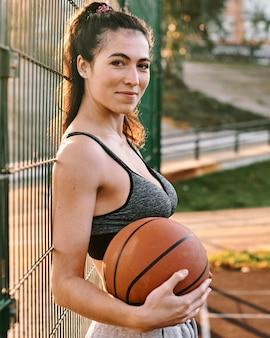 Вид сбоку женщина играет в баскетбол в одиночку