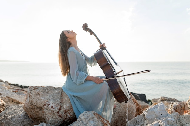 Side view of woman playing cello by the sea