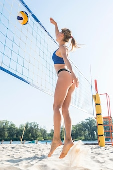 Side view of woman playing volleyball on the beach