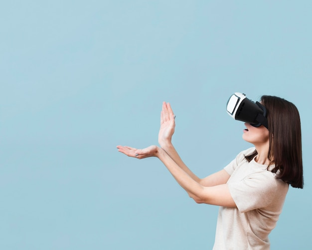 Side view of woman playing while using virtual reality headset with copy space