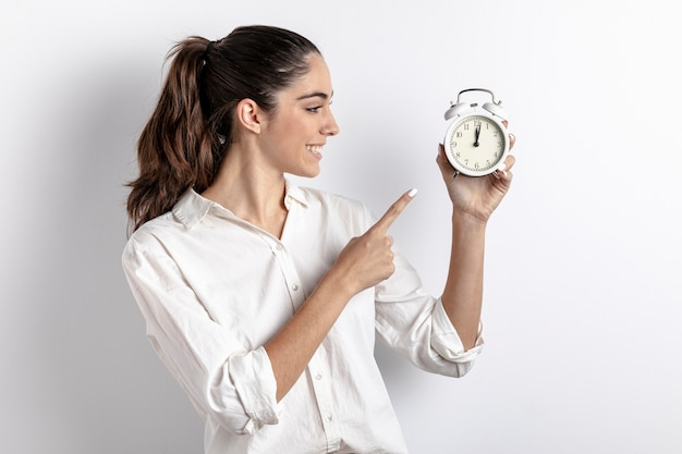 Side view of woman pointing at hand held clock