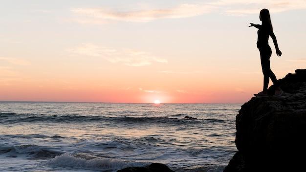 Вид сбоку женщина, указывающая на закат с копией пространства