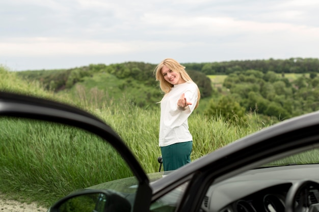 Side view of woman posing in front of car