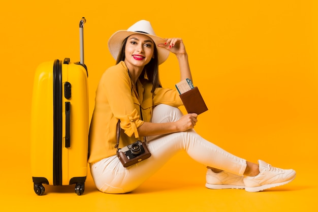 Side view of woman posing next to luggage while holding travel essentials