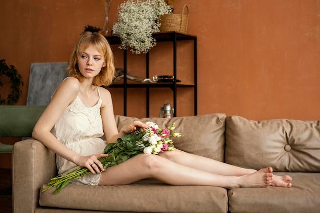 Vista laterale della donna in posa sul divano mentre si tiene il mazzo di fiori primaverili