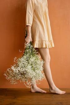 Vista laterale della donna in posa tenendo il mazzo di fiori primaverili