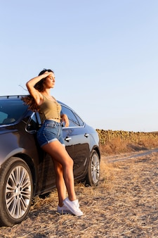 Side view of woman posing while looking at the sun and resting on car