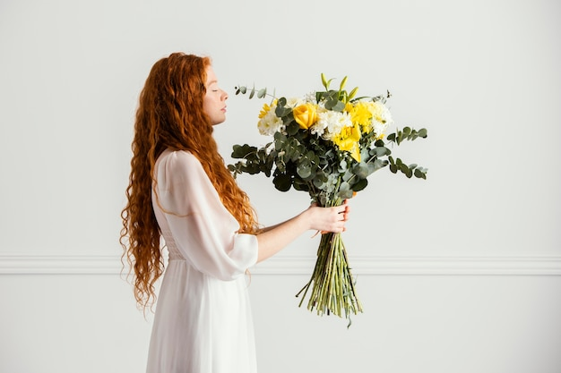 Side view of woman posing with beautiful bouquet of spring flowers