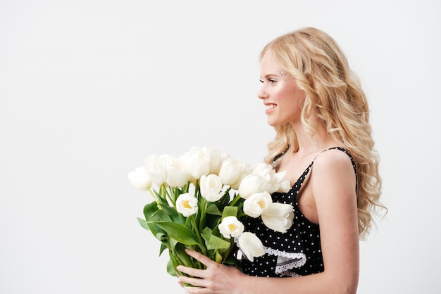 Side view of woman posing with bouquet flowers