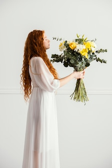 Side view of woman posing with bouquet of spring flowers