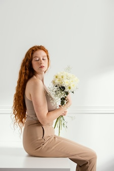 Side view of woman posing with spring flowers on the table