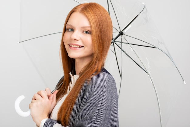 Боковой вид женщина позирует с зонтиком