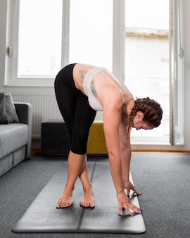 Side view woman practicing yoga at home concept