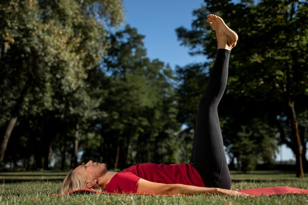 Side view of woman practicing yoga position outdoors