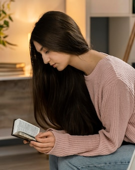 Vista laterale della donna che prega durante la lettura della bibbia