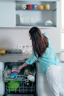 Side view of the woman pulls clean dishes from the dishwasher