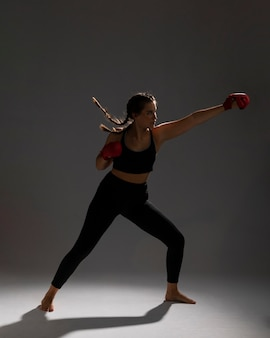 Side view woman punching with box gloves