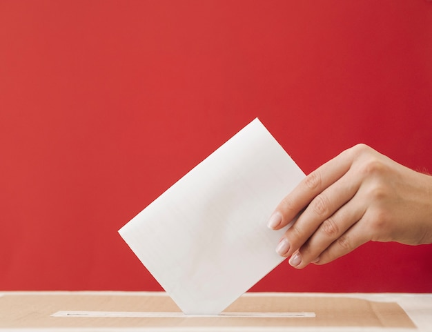 Side view woman putting a ballot in a box with red background