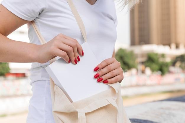 Vista laterale della donna che mette il libro nella sua borsa all'aperto
