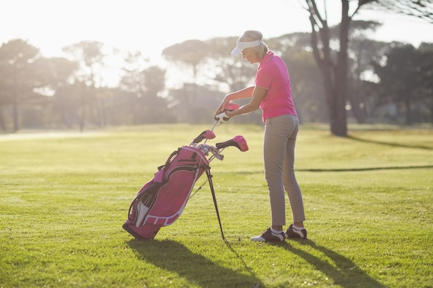 Side view of woman putting golf club in bag