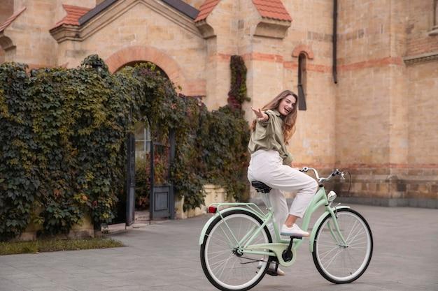 Vista laterale della donna che raggiunge la sua mano mentre guida la sua bicicletta
