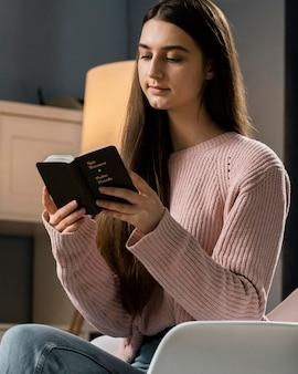 Vista laterale della donna che legge la bibbia