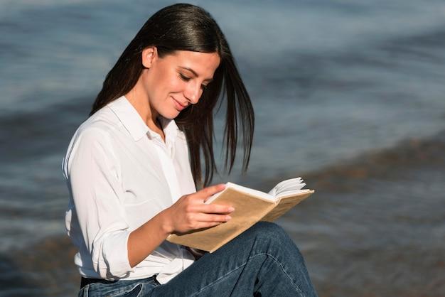 Vista laterale della donna che legge il libro in spiaggia