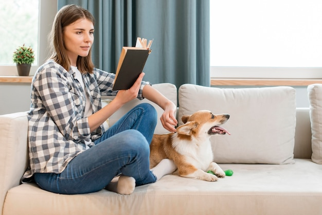 Side view of woman reading book on couch with dog