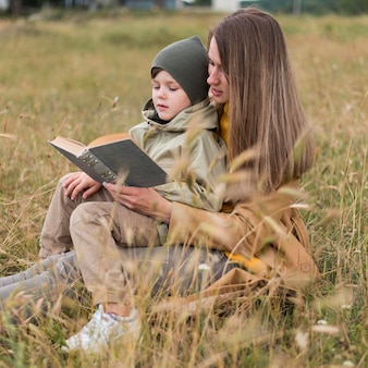 Side view woman reading a book to his son outdoors